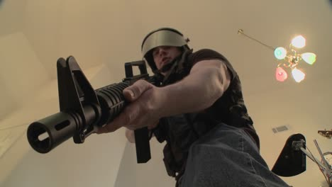 A-SWAT-team-with-DEA-officers-clears-a-house-during-a-drug-raid-and-holds-a-suspect-at-gunpoint