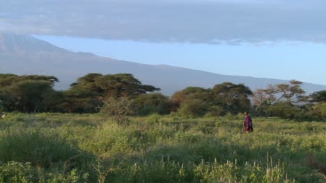 A-Masai-warrior-walks-in-front-of-Mt-Kilimanjaro-in-Tanzania-East-Africa-at-dawn