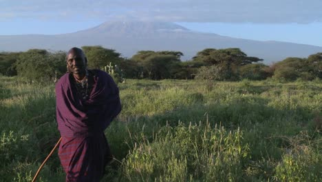 A-Masai-warrior-stands-in-front-of-Mt-Kilimanjaro-in-Tanzania-East-Africa-at-dawn