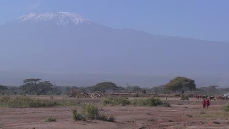 Masai-warriors-walk-in-in-front-of-Mt-Kilimanjaro-in-Tanzania-East-Africa