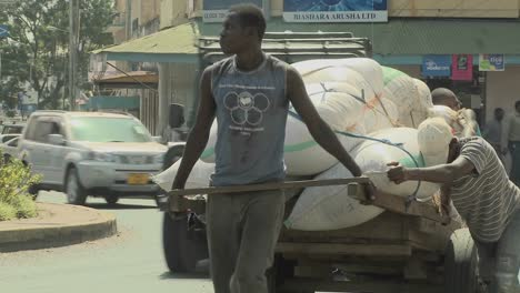 Men-work-hard-to-push-a-cart-up-a-street-in-Arusha-Tanzania