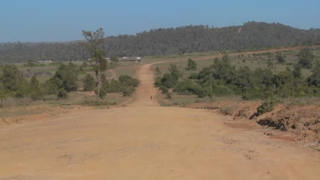 A-man-walks-on-a-lonely-dusty-dirt-road-in-Africa