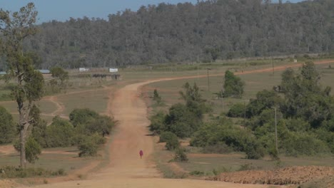 A-man-walks-in-the-distance-on-a-lonely-dusty-dirt-road-in-Africa