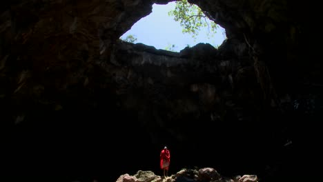 Spectacular-tilt-down-shot-of-a-Masai-warrior-stading-in-a-huge-pool-of-light-in-a-cave-in-Kenya