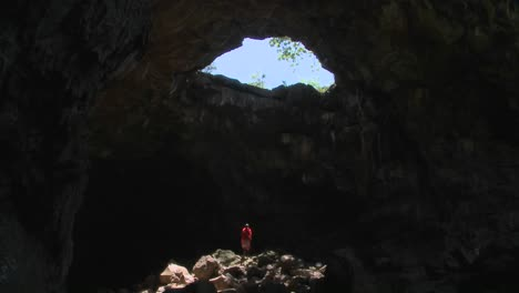 Spectacular-tilt-down-of-a-Masai-warrior-standing-in-a-cave-in-kenya