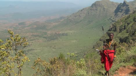 A-Masai-warrior-stands-at-the-edge-of-a-vast-canyon-in-Northern-Kenya