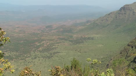 Pan-across-to-a-Masai-warrior-standing-at-the-edge-of-a-vast-canyon-in-Northern-Kenya