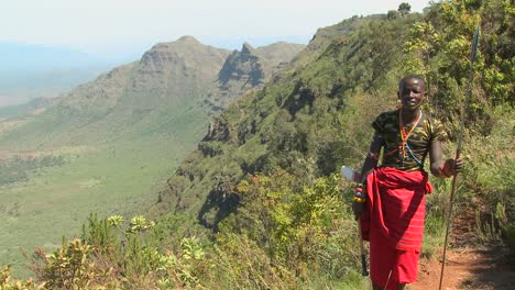Tilt-up-to-reveal-a-Masai-warrior-standing-at-the-edge-of-a-vast-canyon-in-Northern-Kenya