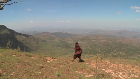 A-masai-warrior-walking-along-a-vast-landscape-in-Northern-Kenya