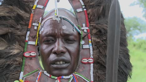Dolly-right-to-reveal-Masai-warrior-face-in-full-headdress-beads-and-spear