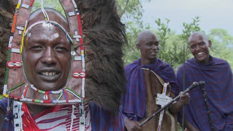Masai-warrior-in-full-headdress-with-two-friends-nearby