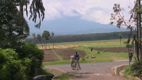 A-man-walks-his-bicycle-down-a-rural-road-in-Rwanda-with-the-Virunga-volcanos-in-the-background