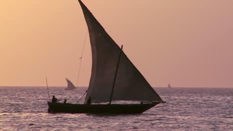 A-beautiful-shot-of-a-dhow-sailboat-sailing-at-sunset-in-Zanzibar