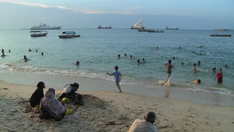 Los-Niños-Juegan-Y-Nadan-En-La-Playa-En-Stone-Town-Zanzibar-Al-Atardecer-Mientras-Los-Veleros-Navegan-En-La-Distancia