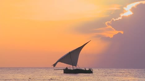 A-beautiful-shot-of-a-dhow-sailboat-sailing-along-the-coast-of-Zanzibar-against-a-beautiful-sunset