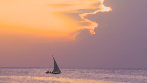 A-beautiful-dhow-sailing-boat-glides-along-the-coast-of-Zanzibar-at-dusk