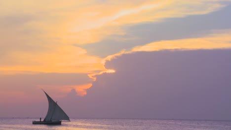 Un-Velero-Dhow-Navega-Por-La-Costa-De-Zanzíbar-Durante-Una-Hermosa-Atardecer-Tropical-A-dhow-sailboat-sails-along-the-coast-of-Zanzibar-during-a-beautiful-tropical-sunset