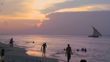 A-dhow-sailboat-sails-along-the-beach-at-Stone-Town-Zanzibar-at-sunset