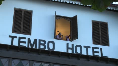 Two-girls-look-out-of-a-tropical-beach-hotel-window