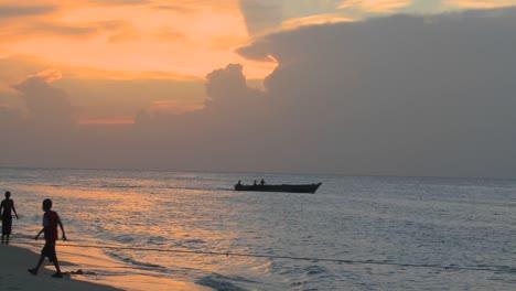 Una-Pequeña-Lancha-Sale-Al-Atardecer-Mientras-La-Gente-Camina-Por-La-Playa-En-Stone-Town-Zanzibar
