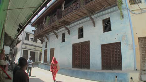 Pedestrians-walk-in-the-narrow-alleys-of-Stone-Town-Zanzibar