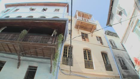 A-low-angle-shot-looking-directly-up-at-tall-old-buildings-lining-the-narrow-alleys-of-Stone-Town-Zanzibar
