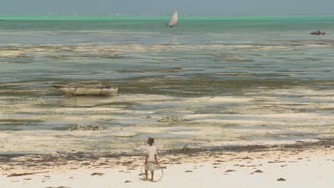 A-girl-stands-with-a-toy-ring-on-the-beach-gazing-out-at-a-distant-sailboat