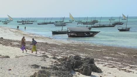 Two-Muslim-women-walk-along-a-beach-in-Zanzibar-with-dhow-sailboats-in-the-background