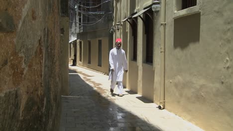 A-Muslim-man-walks-in-the-narrow-alleys-of-Stone-Town-Zanzibar