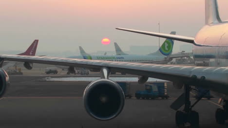 Traffic-moves-on-a-busy-runway-at-sunset-at-an-airport