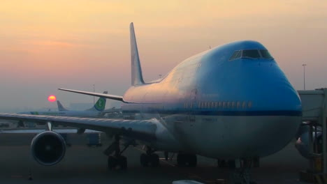 Sunrise-behind-a-modern-747-at-the-boarding-gate-of-an-airport