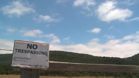 Time-lapse-of-clouds-drifting-past-a-no-trespassing-sign