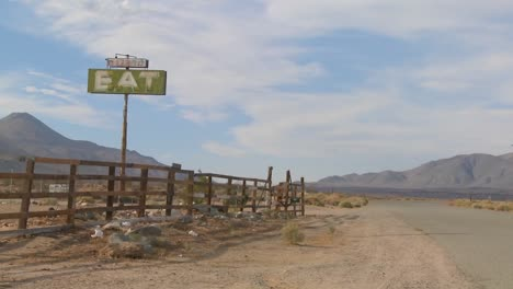 A-slow-zoom-into-an-abandoned-diner-with-a-sign-reading-eat-in-the-Mojave-desert