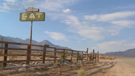 Time-lapse-and-slow-zoom-shot-of-clouds-drifting-past-a-sign-saying-eat-at-an-abandoned-diner