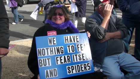 A-woman-holds-a-sign-proclaiming-her-fear-of-spiders