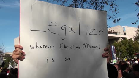 A-man-holds-up-a-sign-saying-legalize-whatever-Christine-ODonnell-is-on-at-the-Jon-Stewart-rally