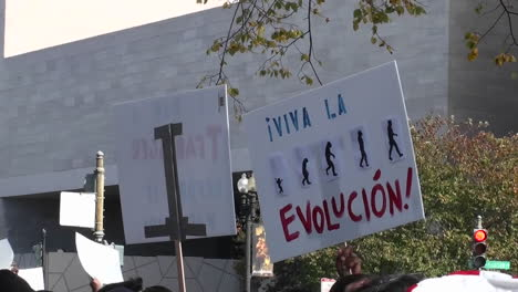 Protestors-hold-signs-at-a-rally-which-include-the-mention-of-tea-baggers-and-evolution