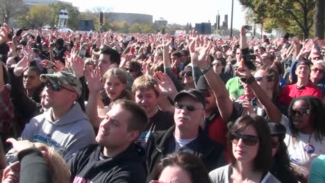 People-wave-their-arms-at-a-giant-outdoor-gathering