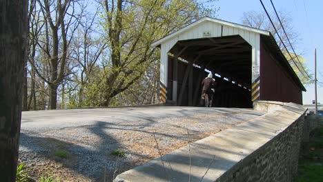 Una-Niña-Amish-Monta-Un-Scooter-De-Pie-A-Través-De-Un-Puente-Cubierto-En-La-Zona-Rural-De-Lancaster-Pennsylvania