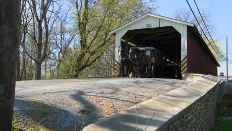 An-Amish-horse-and-buggy-cart-pass-through-a-covered-bridge-in-rural-Lancaster-Pennsylvania-1