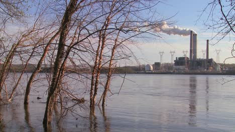 A-power-plant-with-smokestacks-near-a-river