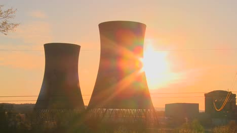Time-lapse-shot-of-the-sun-setting-behind-a-nuclear-power-plant