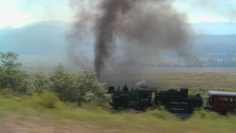 Traveling-shot-of-a-steam-train-moving-through-the-Rocky-Mountains