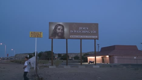 A-billboard-advertising-Jesus-is-watching-you-near-an-adult-video-store