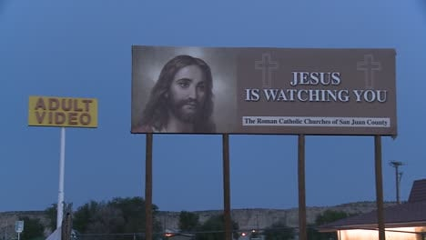 A-billboard-advertising-Jesus-is-watching-you-near-an-adult-video-store-1