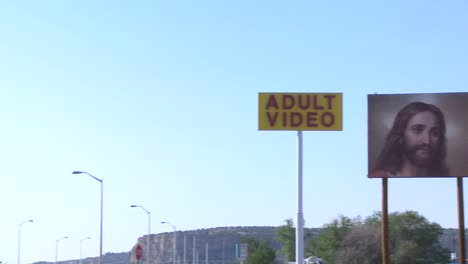 A-billboard-advertising-Jesus-is-watching-you-near-an-adult-video-store-3