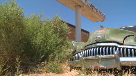 A-slow-moving-shot-tracking-along-an-old-rusted-car-at-an-abandoned-trading-post-1