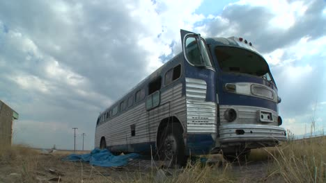 A-moving-time-lapse-shot-of-an-abandoned-Greyhound-bus-in-a-field