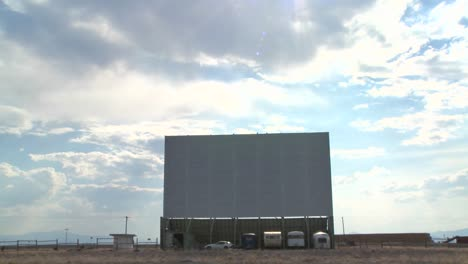 A-time-lapse-shot-of-clouds-passing-over-an-abandoned-drive-in-theater-screen