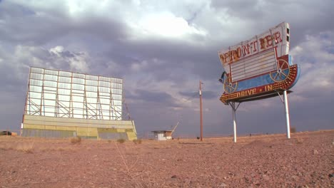 Clouds-pass-over-an-abandoned-drive-in-sign-and-screen